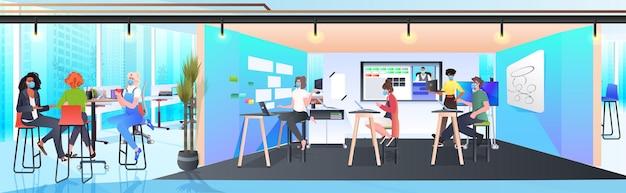 Zakenmensen in maskers werken en praten samen in coworking center coronavirus pandemie teamwerk concept modern kantoor interieur horizontaal volledige lengte