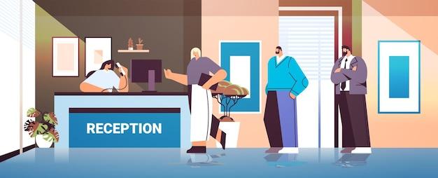 Zakenmensen, klanten of reizigers die bij de receptie staan en praten met de receptioniste