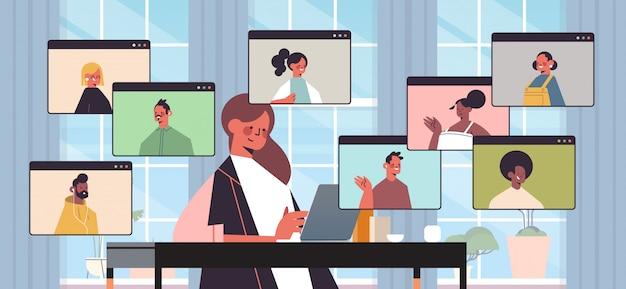 Zakenvrouw chatten met mix race collega's tijdens video-oproep mensen uit het bedrijfsleven hebben online conferentie vergadering communicatieconcept kantoor interieur horizontale portret illustratie