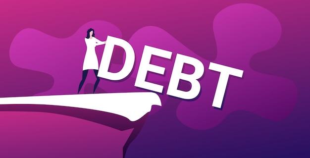 Zakenvrouw duwen schuld woord in afgrond financiële vrijheid concept horizontale volledige lengte