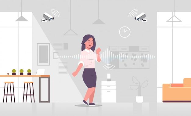 Zakenvrouw met cctv camera bestuurd door slimme spreker stemherkenning