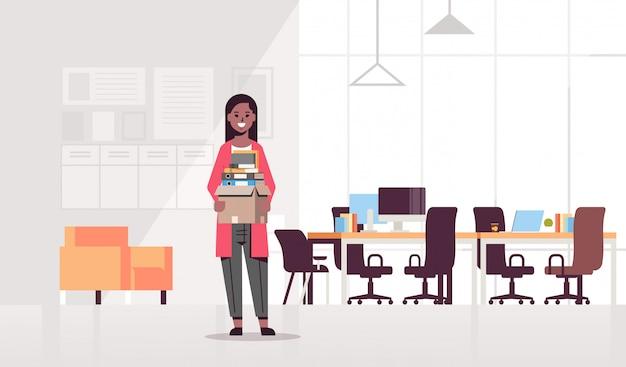 Zakenvrouw met doos met spullen dingen nieuwe baan bedrijfsconcept creatieve co-working center moderne werkplek kantoor interieur volledige lengte horizontaal
