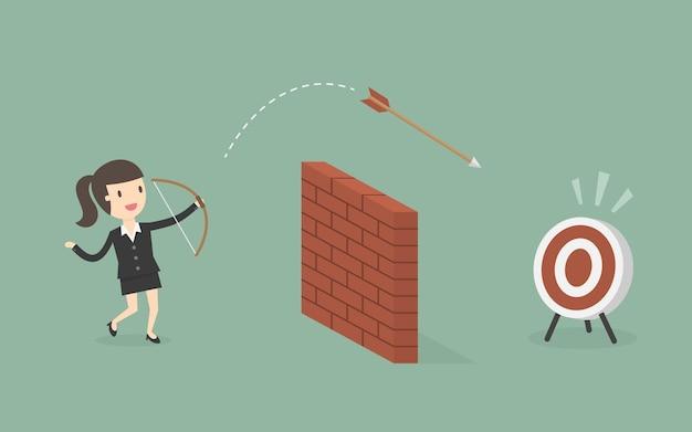 Zakenvrouw schiet pijl over de muur naar het doel.