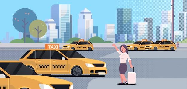 Zakenvrouw vangen taxi op straat zakenvrouw in formele slijtage met bagage gele taxi stad vervoer service stadsgezicht stoppen