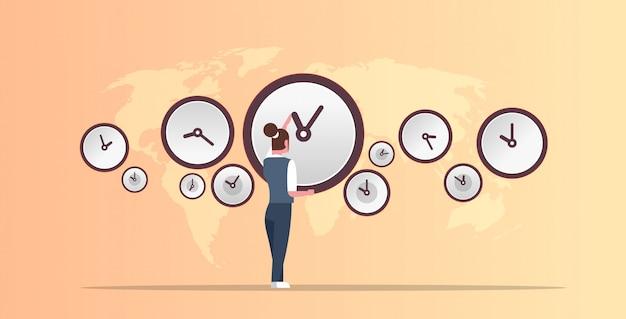 Zakenvrouw wijzend op de muur met klokken verschillende steden tijd beheer deadline concept wereldkaart achtergrond horizontale volledige lengte