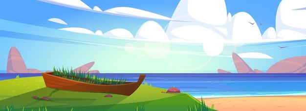Zeestrand met oude boot in groen gras