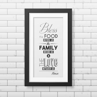 Zegen het eten dat voor ons ligt - typografisch citaat in realistische vierkante zwarte lijst op de bakstenen muur.