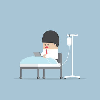 Zieke zakenman die hard in het ziekenhuisbed werkt