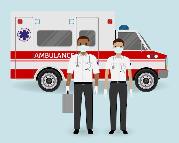 Ziekenhuispersoneel concept. paramedici ambulance team met medische bescherming maskers op ambulance auto achtergrond