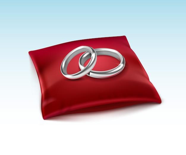 Zilveren trouwringen op rood satijn kussen geïsoleerd op wit