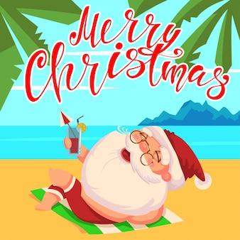 Zomer santa claus in korte broek en met een cocktail in zijn hand ligt op het strand.