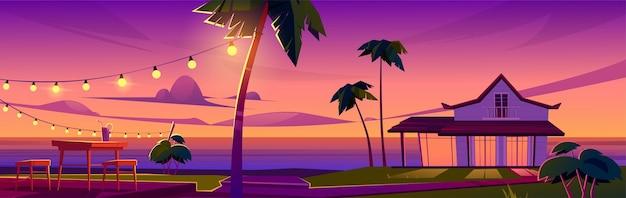 Zomer tropisch landschap met bungalow op oceaan strand, tafel en stoelen op terras bij zonsondergang