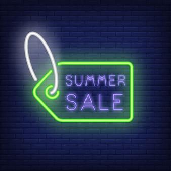 Zomer verkoop neon teken. creatieve belettering binnenkant van groene tag op donker blauwe bakstenen muur. nacht helder