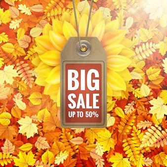 Zonnebloem op de herfstgebladerte met verkoopmarkering.
