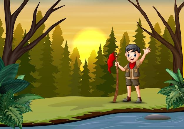 Zonsondergang bij bosachtergrond met een verkennersjongen