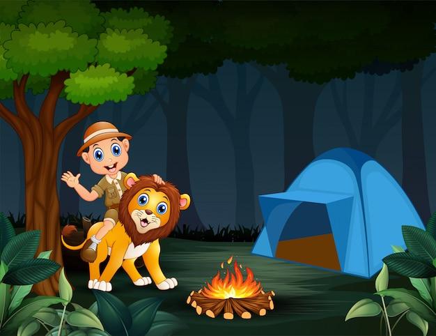 Zookeeper jongen en een leeuw in de jungle in de nacht