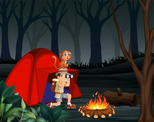 Zookeeperjongen en zijn aap die in een donker bos kamperen