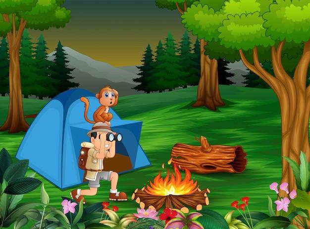Zookeeperjongen en zijn aap die in het donkere bos kamperen