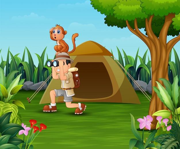 Zookeeperjongen en zijn aap die in het mooie park kamperen
