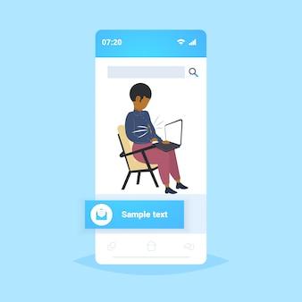 Zwaarlijvige zakenman met dikke buik met laptop overgewicht afro-amerikaanse zakenman zittend op fauteuil ongezonde levensstijl zwaarlijvigheid concept smartphone scherm mobiele app volledige lengte