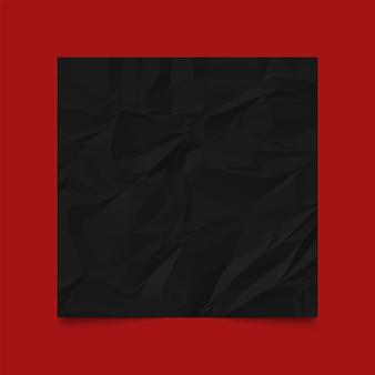 Zwart verfrommeld papier op rood frame.