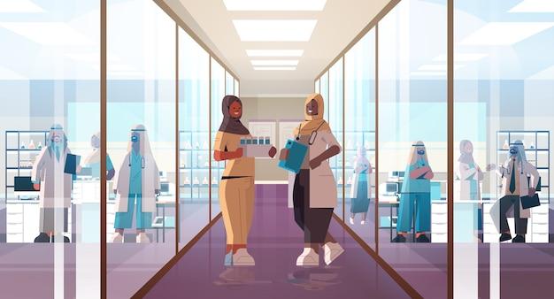 Zwarte afrikaanse moslim artsen in uniform bespreken tijdens bijeenkomst in ziekenhuis gang geneeskunde gezondheidszorg concept horizontale volle lengte vectorillustratie