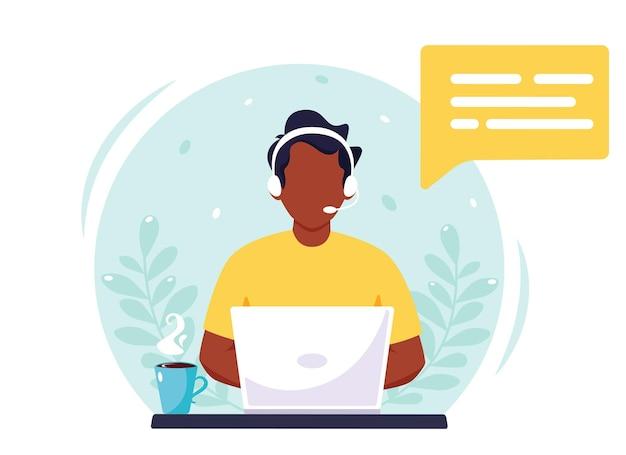 Zwarte man met koptelefoon die op computer werkt