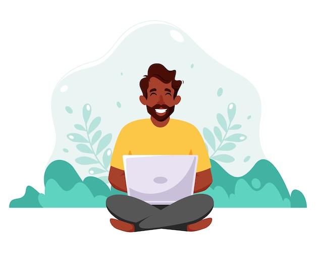 Zwarte man zit met laptop. freelance, online studeren, overal thuis werken. illustratie in vlakke stijl.