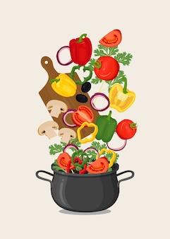 Zwarte pan met kokend water en groenten, snijplank
