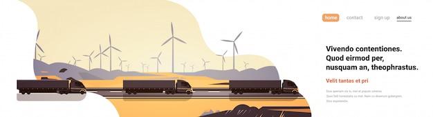 Zwarte semi vrachtwagenaanhangwagens die van het windturbineslandschap van het wegplatteland de ruimte van het de bannerexemplaar drijven