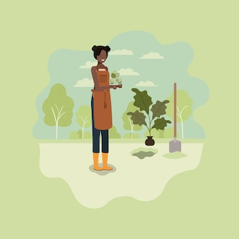 Zwarte vrouw aanplant boom in het park