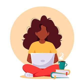 Zwarte vrouw die op laptop werkt. freelance, werken op afstand, online studeren.