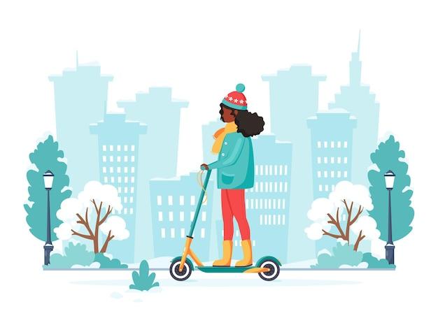Zwarte vrouw elektrische kick scooter rijden in de winter