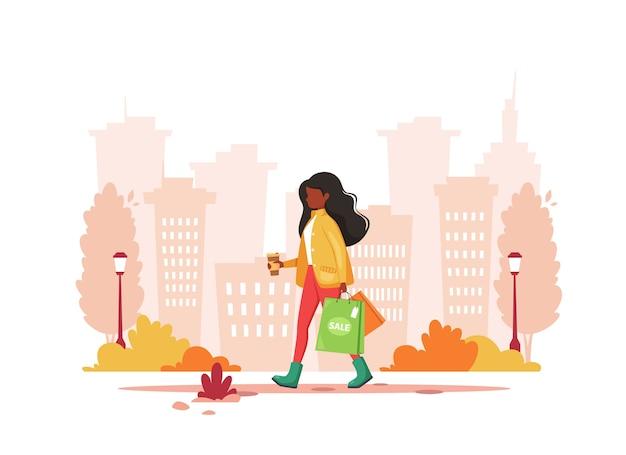 Zwarte vrouw winkelen in de stad met koffie. stedelijke levensstijl.