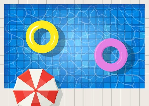 Zwembad met zomerparasol en zwemring. wateroppervlak bovenaanzicht